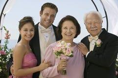 Novia y novio con los padres fotos de archivo