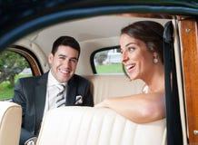 Novia y novio dentro de un coche clásico Foto de archivo