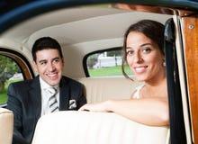 Novia y novio dentro de un coche clásico hermoso Fotos de archivo libres de regalías