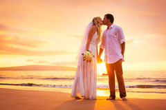Novia y novio, disfrutando de puesta del sol asombrosa en un tropical hermoso Imagenes de archivo