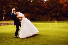 Novia y novio divertidos en campo del golf Fotografía de archivo libre de regalías