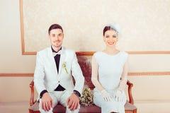 Novia y novio elegantes jovenes en el sofá fotos de archivo libres de regalías