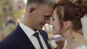 Novia y novio elegantes junto en una iglesia vieja Pares de la boda metrajes