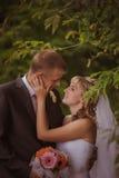 Novia y novio en besarse del parque los recienes casados novia y novio de los pares en una boda en bosque del verde de la natural Foto de archivo libre de regalías