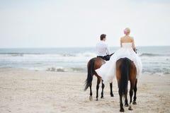 Novia y novio en caballos por el mar Foto de archivo libre de regalías