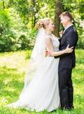 Novia y novio en el día de boda que caminan al aire libre Abarcamiento feliz de los recienes casados Pares cariñosos Imagen de archivo