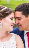 Novia y novio en el día de boda que caminan al aire libre Abarcamiento feliz de los recienes casados Pares cariñosos Foto de archivo