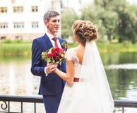Novia y novio en el día de boda que caminan al aire libre Abarcamiento feliz de los recienes casados Pares cariñosos Imagenes de archivo