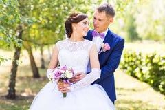 Novia y novio en el día de boda que caminan al aire libre Abarcamiento feliz de los recienes casados Pares cariñosos Imagen de archivo libre de regalías