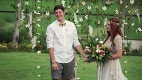 Novia y novio en la ceremonia de boda Jardín tropical en la tarde Pares preciosos de los recienes casados metrajes