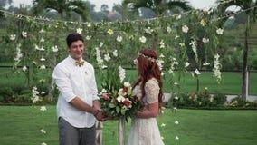 Novia y novio en la ceremonia de boda Jard?n tropical en la tarde Pares preciosos de los recienes casados almacen de metraje de vídeo