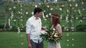 Novia y novio en la ceremonia de boda Jard?n tropical en la tarde Pares preciosos de los recienes casados metrajes