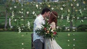 Novia y novio en la ceremonia de boda Jard?n tropical en la tarde Pares preciosos de los recienes casados almacen de video