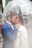 Novia y novio en la lluvia mientras que sonríe y mira el uno al otro Foto de archivo libre de regalías