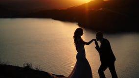 Novia y novio en la montaña en la puesta del sol almacen de metraje de vídeo
