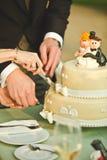 Novia y novio en la recepción nupcial que corta el pastel de bodas Imagen de archivo