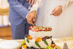 Novia y novio en la recepción nupcial que corta la torta Imágenes de archivo libres de regalías