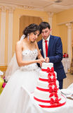 Novia y novio en la recepción nupcial que corta la torta Imagen de archivo