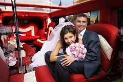 Novia y novio en limusina de la boda Imagenes de archivo