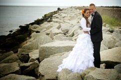Novia y novio en rocas, mar Báltico Fotos de archivo libres de regalías