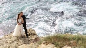 Novia y novio en un acantilado sobre el océano almacen de metraje de vídeo