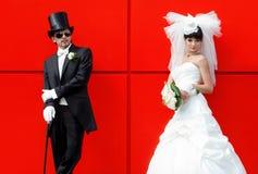 Novia y novio en un fondo rojo Fotografía de archivo libre de regalías