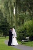 Novia y novio en un parque Imágenes de archivo libres de regalías