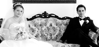 Novia y novio en un sofá fotos de archivo