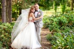 Novia y novio en un vestido blanco en el parque foto de archivo