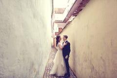 Novia y novio en una calle estrecha Imágenes de archivo libres de regalías