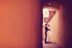 Novia y novio en una calle estrecha Fotos de archivo libres de regalías