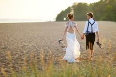 Novia y novio en una playa en la puesta del sol Fotografía de archivo