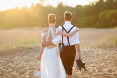Novia y novio en una playa en la puesta del sol imagen de archivo libre de regalías