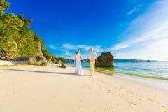 Novia y novio en una playa tropical con la puesta del sol en el backg Fotografía de archivo