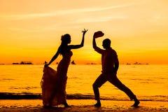 Novia y novio en una playa tropical con la puesta del sol en el backg Fotos de archivo