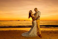 Novia y novio en una playa tropical con la puesta del sol en el backg Foto de archivo libre de regalías