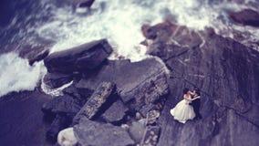 Novia y novio en una roca grande cerca del mar Foto de archivo libre de regalías