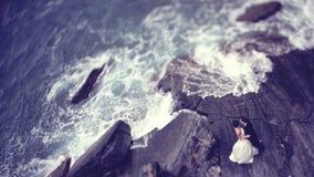 Novia y novio en una roca grande cerca del mar Imagenes de archivo