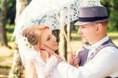 Novia y novio felices con el paraguas en un bosque Imagen de archivo