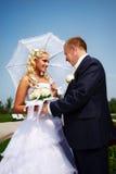 Novia y novio felices en el cielo azul del fondo Imagen de archivo