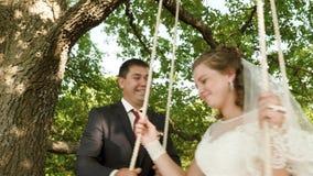 Novia y novio felices en el vestido blanco que balancea en el oscilación en parque del verano oscilación en rama de un roble en b almacen de metraje de vídeo