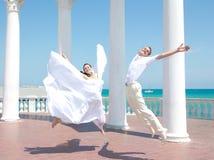 Novia y novio felices en salto Foto de archivo libre de regalías