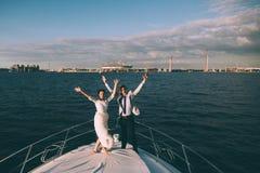 Novia y novio felices en un yate que viaja junto Fotografía de archivo