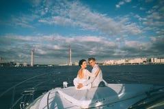 Novia y novio felices en un yate que viaja junto Foto de archivo libre de regalías