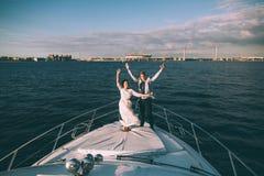 Novia y novio felices en un yate que viaja junto Imagen de archivo libre de regalías