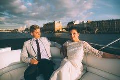 Novia y novio felices en un yate que viaja junto Foto de archivo