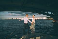 Novia y novio felices en un yate que viaja junto Fotos de archivo