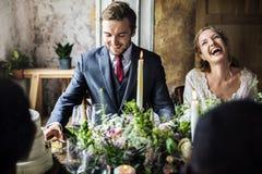 Novia y novio Having Meal con los amigos en la recepción nupcial Fotos de archivo