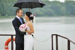 Novia y novio jovenes en un día lluvioso Imagenes de archivo