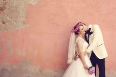 Novia y novio que abrazan cerca de la pared Imágenes de archivo libres de regalías